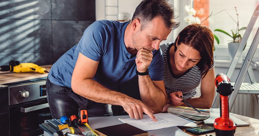 A couple planning a kitchen renovation with plans and tools surrounding them.