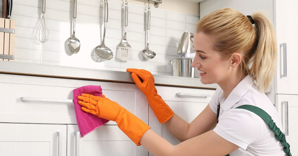 Woman cleaning cabinets in a white kitchen.