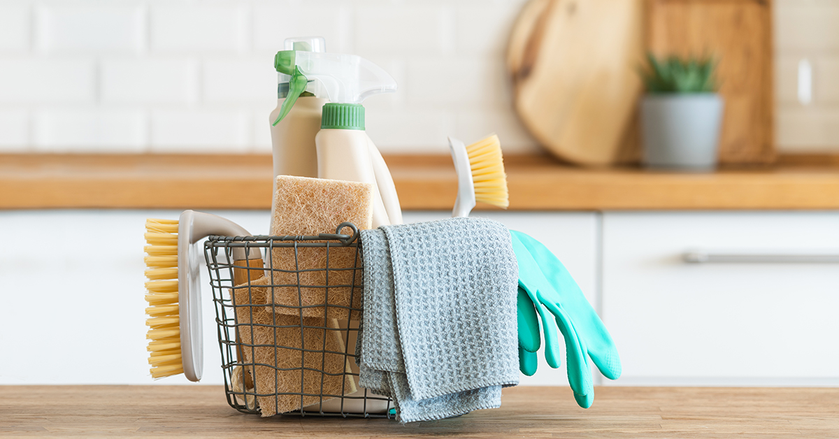 Basket of cleaning supplies on a kitchen counter.