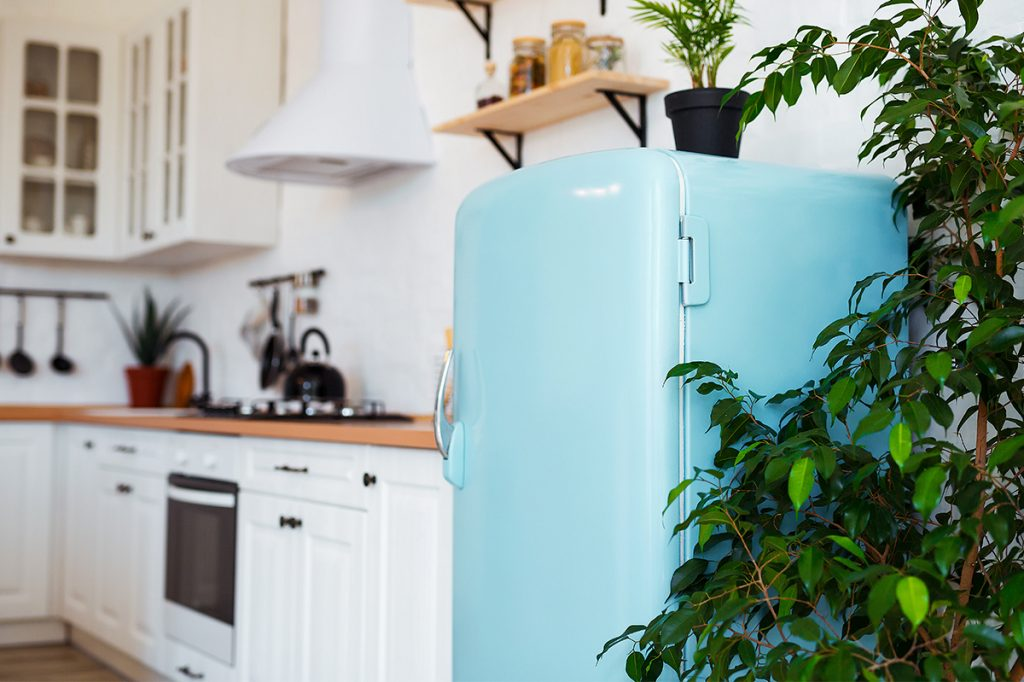 White kitchen with robin egg-blue retro style refrigerator in the foreground.