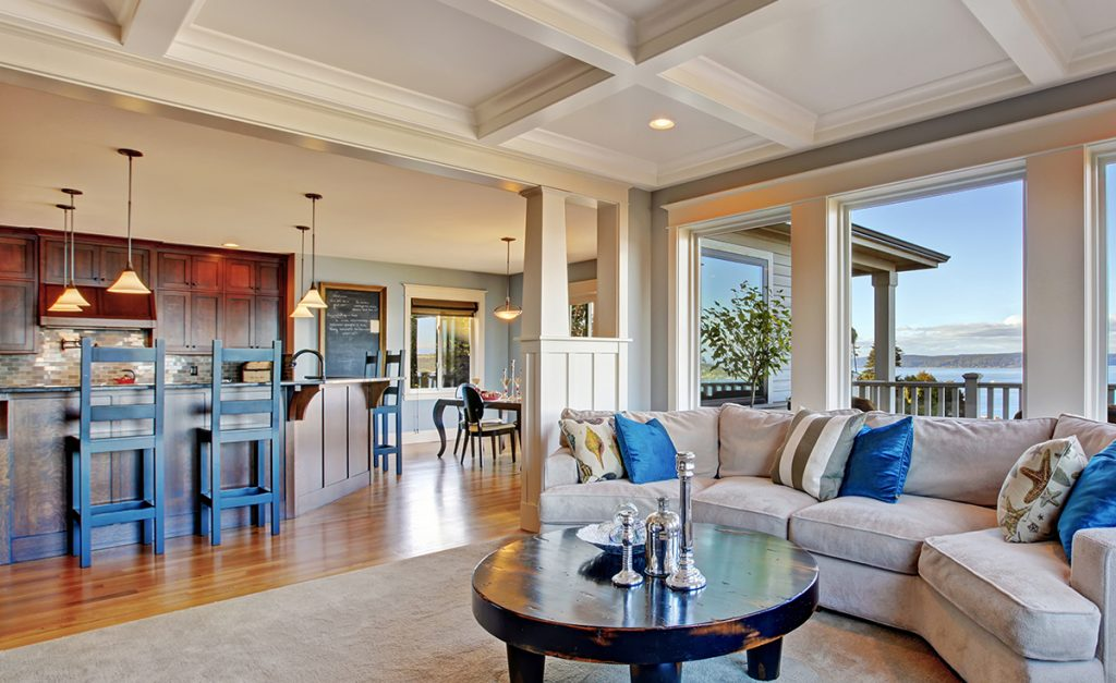 Coffered ceilings and other architectural elements give this open format kitchen/living room definite transitional flavor.