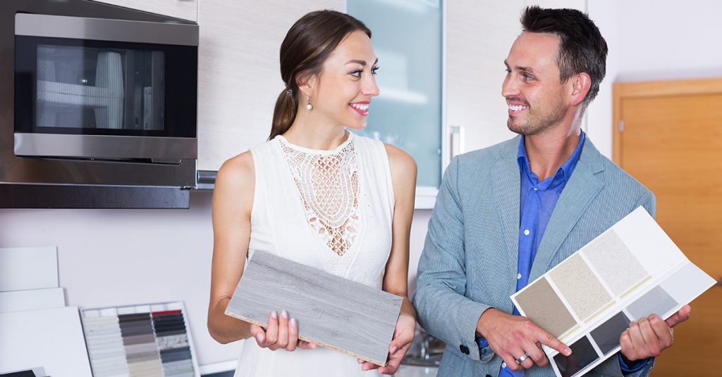 Two people comparing samples for a kitchen remodel.