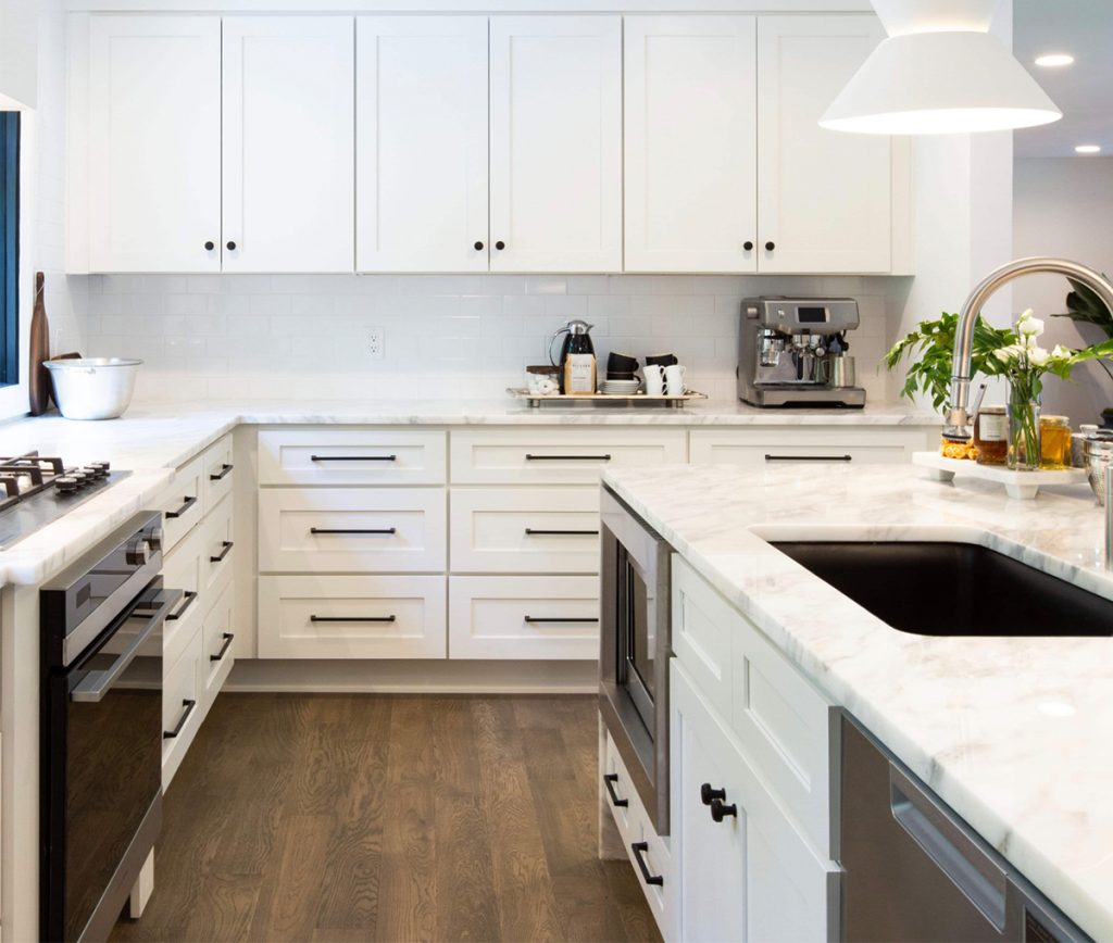 Large, white kitchen with dark contrasting hardware.