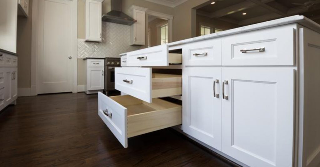 White cabinets and drawers in an island.
