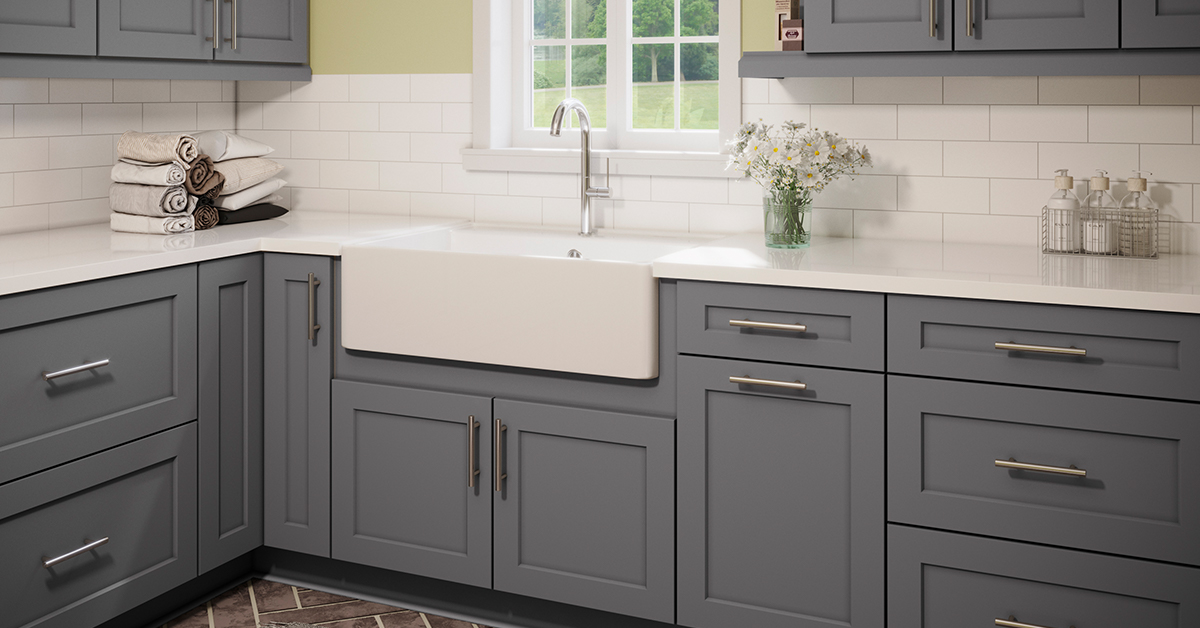 Gray kitchen cabinets with a white farmhouse sink in an open kitchen layout.