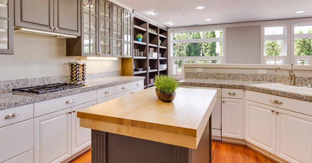 Gray cabinets on the wall and island contrast with white base cabinets.
