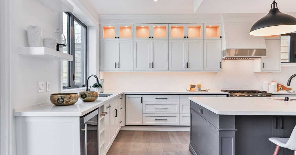 Cabinets in this white kitchen go from the floor all the way flush with the ceiling.