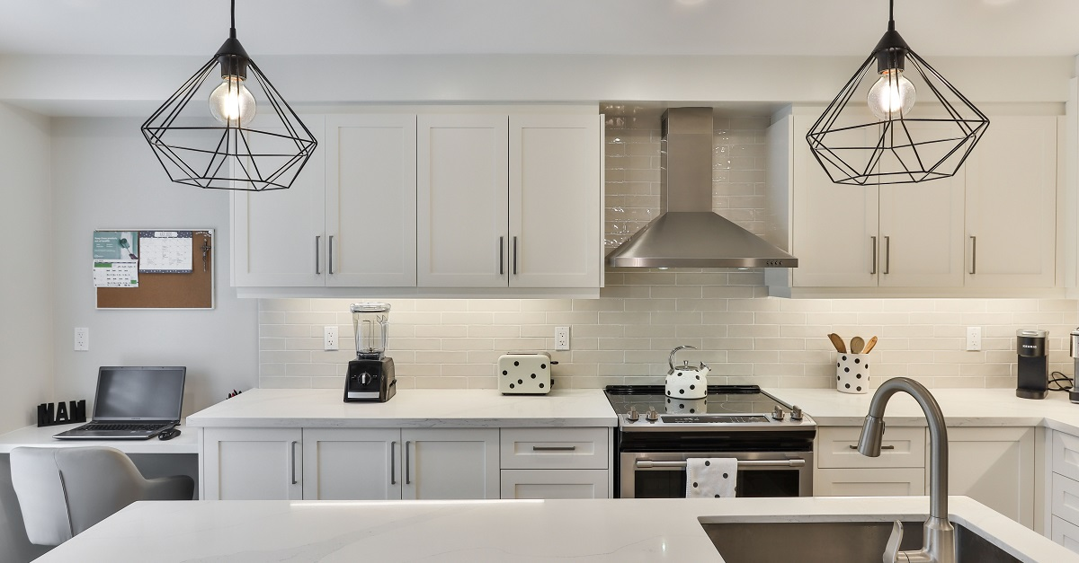 Multi-tasking kitchen with work space and statement lighting.