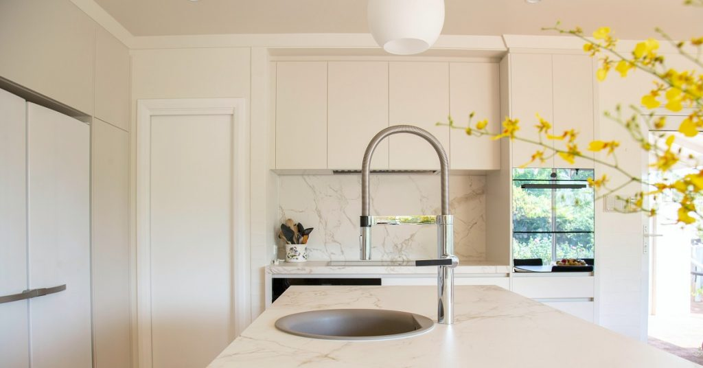 Dramatic marble backsplash and seamless flat panel cabinets in a white kitchen.