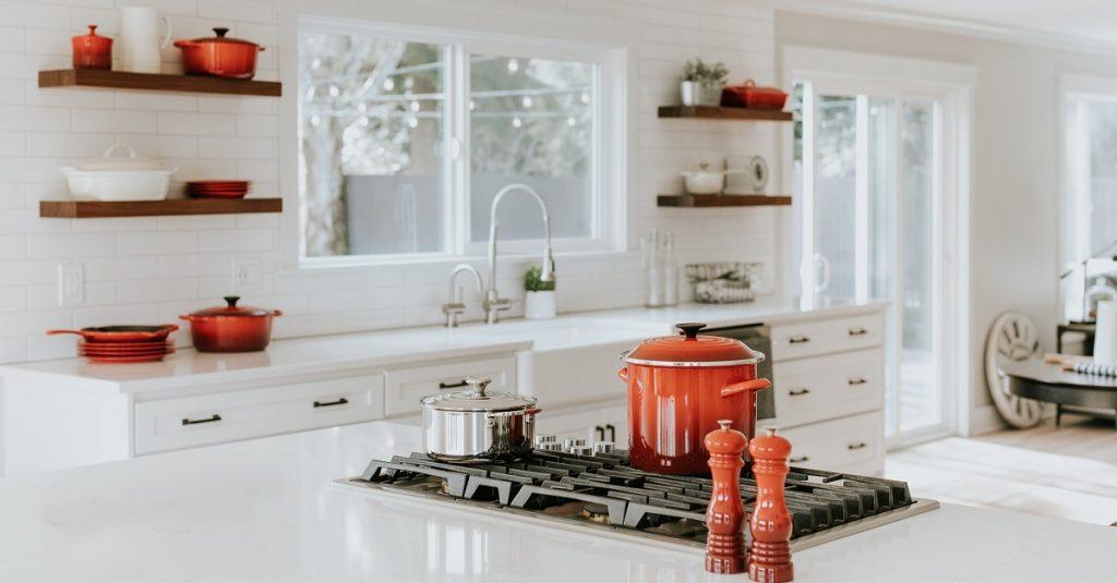 Pops of bright red/orange in a white modern kitchen.