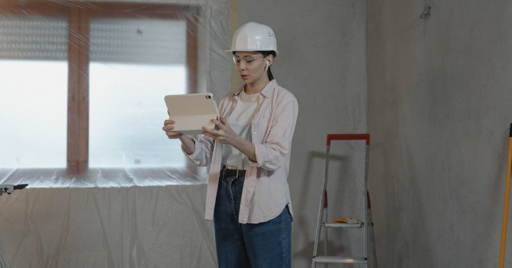 Woman planning a remodel in an empty room ready for construction.
