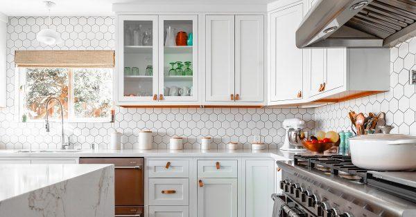 White kitchen with full wall backsplash of hexagon mosaic tiles.