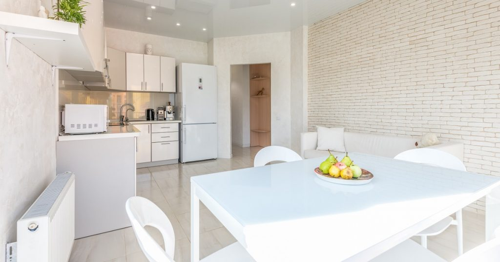 All white kitchen with textured brick feature wall.