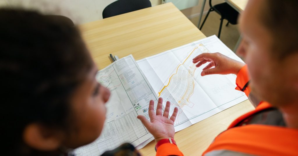 A homeowner and contractor review plans.