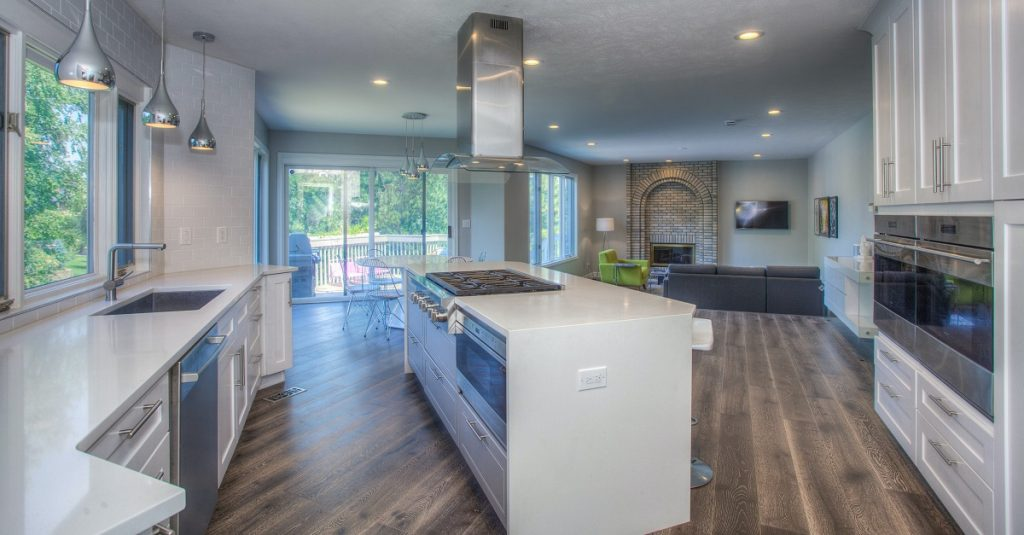 White kitchen with easy access to sink, stovetop, and ovens.