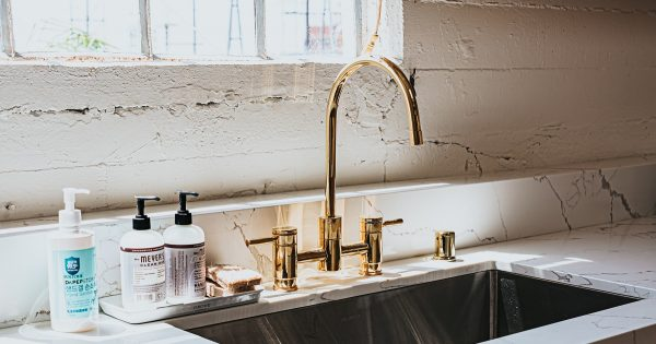 Gold colored kitchen faucet and fixtures in a white retro kitchen.