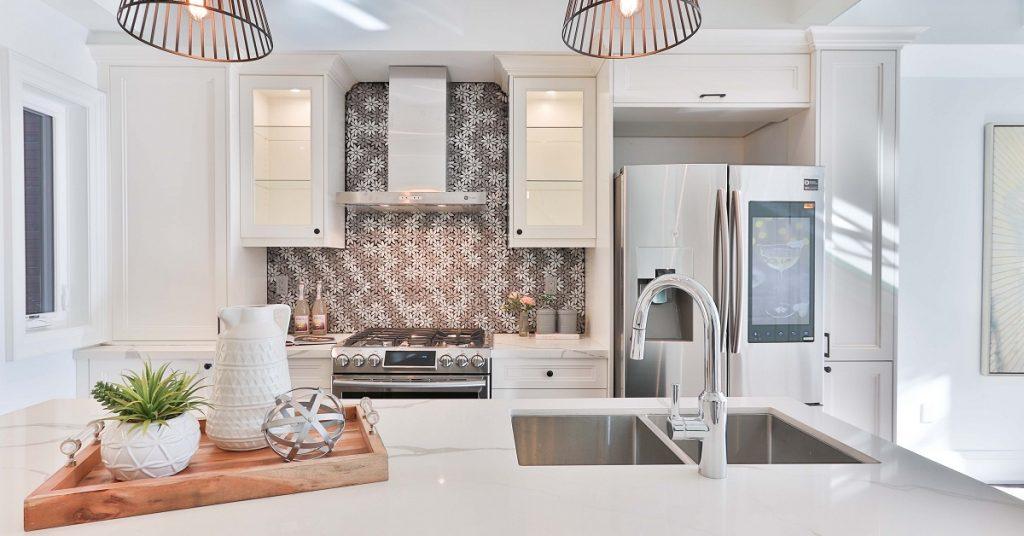 White kitchen with floral tile backsplash.