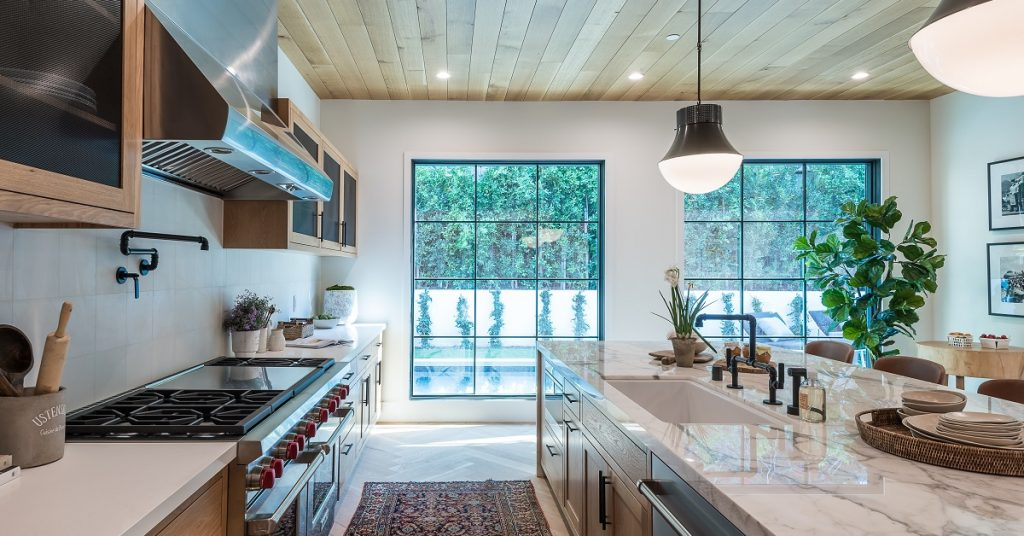 Galley kitchen with a rug and wood planks on the walls.