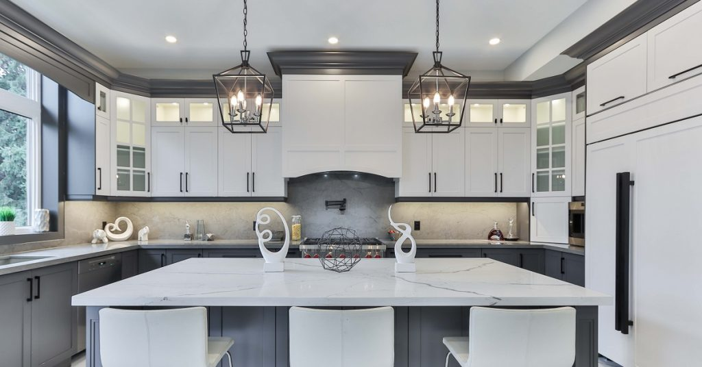 Gray and white kitchen with statement pendant lights over the island.