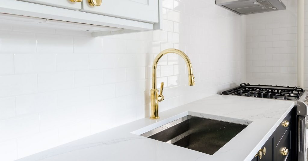 White kitchen with gold faucet at the kitchen sink.