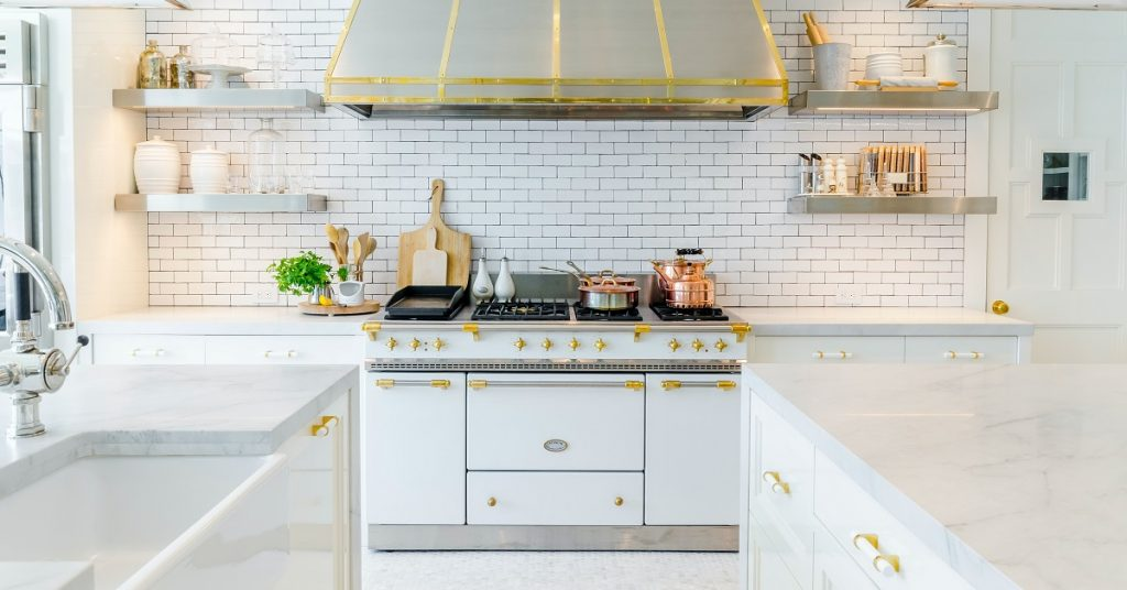 White and gold kitchen with new drawer pulls and open shelving.